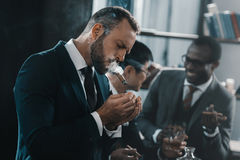 Businessman smoking cigar with multicultural business team. Spending time behind Stock Image