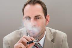 Businessman smoking electronic cigarette Royalty Free Stock Photography