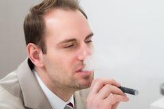 Businessman smoking electronic cigarette Stock Photos