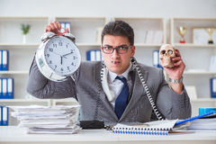 Businessman smoking holding human skull and an alarm clock in th Stock Images