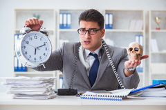 Businessman smoking holding human skull and an alarm clock in th Stock Photo