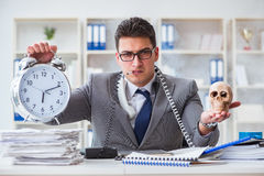 Businessman smoking holding human skull and an alarm clock in th Royalty Free Stock Image