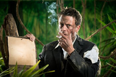 Businessman smoking in the jungle Royalty Free Stock Image