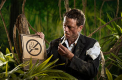 Businessman smoking in the jungle Stock Image