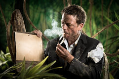 Businessman smoking in the jungle Royalty Free Stock Photography