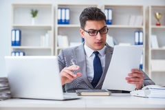 The businessman smoking in office at work Stock Images
