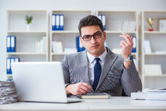 The businessman smoking in office at work Stock Photo