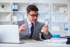 The businessman smoking in office at work Royalty Free Stock Photos