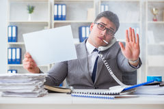 Businessman smoking at work in office holding a blank message bo Stock Image
