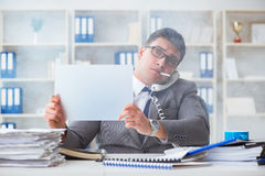 Businessman smoking at work in office holding a blank message bo Stock Photos