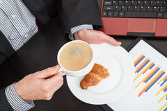 Businessman with snack and coffee Royalty Free Stock Photography