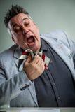 Businessman sneezing on his necktie Stock Images