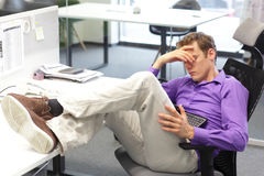 Businessman snoozing over his tablet in office. Young tired  businessman snoozing over his tablet in office Stock Image