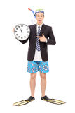 Businessman with a snorkel holding wall clock stock photos