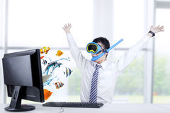 Businessman with snorkeling mask. Shocked businessman with snorkeling mask looking at fishes coming out from computer screen Stock Image