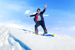 Businessman snowboarding on top of a mountain Royalty Free Stock Photography