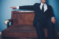 Businessman on sofa pointing left Royalty Free Stock Photo