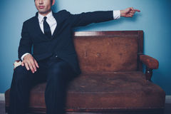 Businessman on sofa pointing right Stock Photography