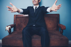 Businessman on sofa is ready for a hug Stock Images