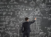 Businessman solve problems with Math calculations. Businessman trying to solve problems with Math calculations on the blackboard Royalty Free Stock Photo