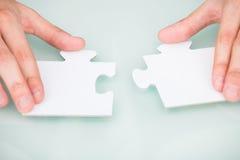 Businessman solving jigsaw puzzle Stock Photo