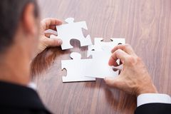 Businessman Solving Jigsaw Puzzle Stock Images