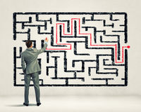 Businessman solving labyrinth problem Stock Image