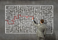 Businessman solving labyrinth problem Stock Images