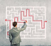 Businessman solving labyrinth problem Stock Photography