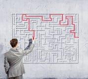 Businessman solving labyrinth problem Stock Image