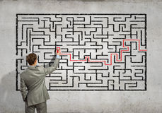 Businessman solving labyrinth problem Stock Photo