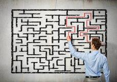 Businessman solving labyrinth problem Stock Images