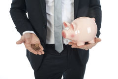 Businessman with some coins and piggy-bank. A businessman expressing poverty, he holds some coins and a piggy-bank in his hand stock photography
