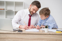 Businessman with son drawing at table stock photos
