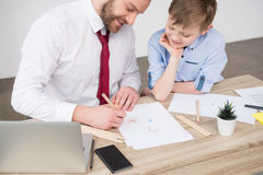 Businessman with son drawing at table Royalty Free Stock Images