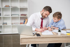 Businessman with son drawing at table Royalty Free Stock Photography