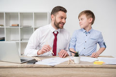 Businessman with son drawing at table Stock Photo