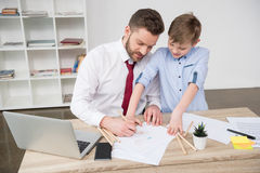 Businessman with son drawing at table Stock Image