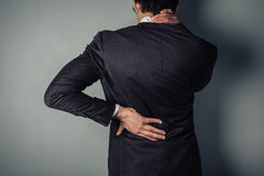 Businessman with sore back and neck. Young businessman with a sore neck and back Royalty Free Stock Photos