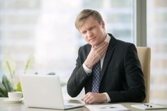 Businessman with sore throat. Young businessman working with laptop at desk in the office, hand at his neck, feeling unwell, have a sore throat, after loud Royalty Free Stock Images