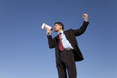 Businessman speaking with a megaphone. With the blue sky as background (wide format photo Stock Photo