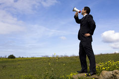 Businessman speaking with a megaphone. In a field Stock Images