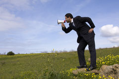 Businessman speaking with a megaphone. In a field Royalty Free Stock Photos