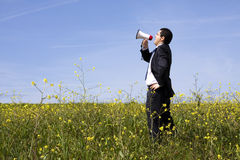 Businessman speaking with a megaphone. In a field Royalty Free Stock Photography