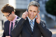 Businessman Speaking On Mobile Phone In Noisy Surroundings. Standing stock images
