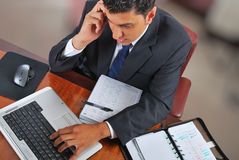 Businessman speaking over the phone. Young businessman working on a laptop and speaking on mobile phone Stock Photo