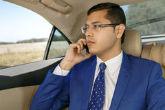 Businessman speaking on phone in backseat of car. Young businessman sitting in the back-seat of a car, speaking on his phone Royalty Free Stock Photos