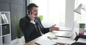 Businessman speaking on phone call. Young businessman speaking on mobile phone at office desk stock video