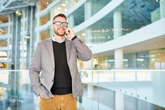 Businessman Speaking by Phone in Office Building. Portrait of cheerful modern businessman speaking by phone and smiling while standing at glass balcony in office Royalty Free Stock Image