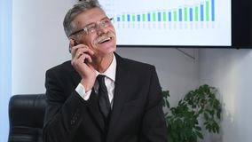 Businessman speaking on the phone in office in front of desktop Royalty Free Stock Photo